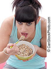 Young woman eating bowl of healthy breakfast cereal