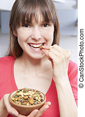 Young Woman Eating Bowl Of Healthy Seeds