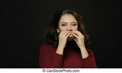 Young woman eating burger, closeup shooting
