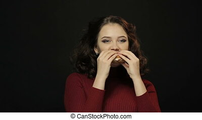 Young woman eating burger, closeup shooting