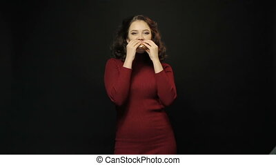 Young woman eating burger on black background