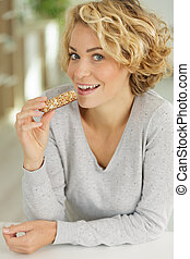 young woman eating cereal bar