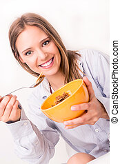 Young woman eating cereals for breakfast in bed