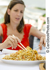 Young woman eating chinese noodles