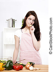 young woman eating cucumber while preparing salad