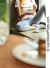 Young woman eating delicious cake on italian restaurant.