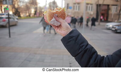 Young woman eating fast food outdoor , hamburger in hand