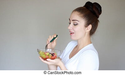 Young woman eating fork salad from fresh vegetables. Health, vegetarian, fitness and diet concept. Vegetarian food