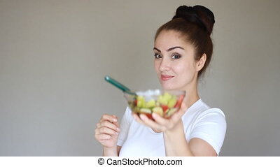 Young woman eating fork salad from fresh vegetables. Health,...