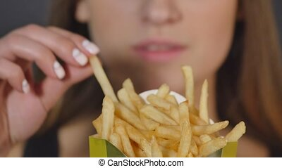 young woman eating french fries close detail