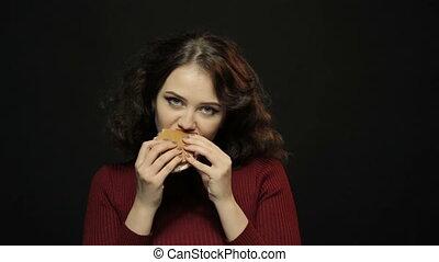 Young woman eating hamburger, closeup shooting