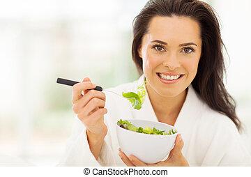 beautiful young woman in bathrobe eating healthy food