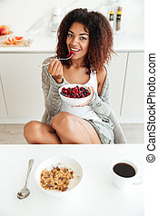 Young woman eating healthy food in kitchen