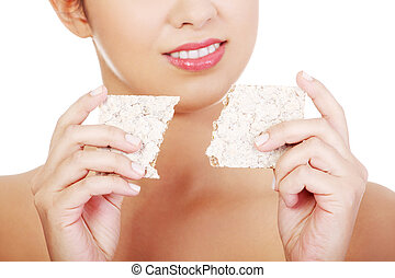 Young woman eating healthy rye cracker bread