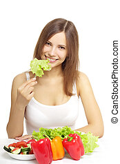 Young woman eating healthy salad on white