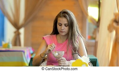 Young woman eating ice cream in a cafe.