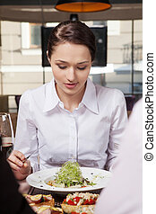 Young woman eating mixed vegetable salad in cafe. Woman eating healthy salad lunch in cafe with friends