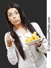 young woman eating potatoe chips against a black background