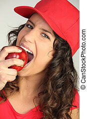young woman eating red apple