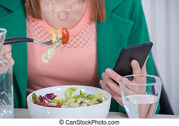 young  woman eating salad and phone