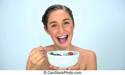 Young woman eating salad on white background
