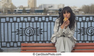 Young woman eating sandwich on bench