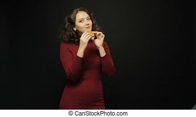 Young woman eating sandwich on black background