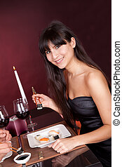 Young woman eating sushi in restaurant