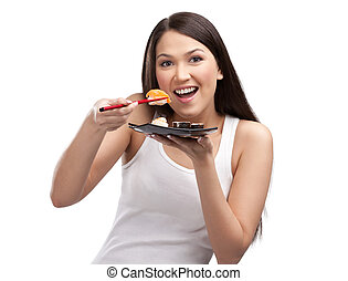 Young woman eating sushi with a chopsticks