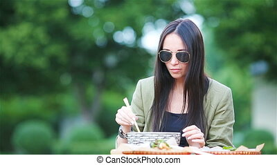 Young woman eating take away noodles on the street -...