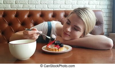 Young Woman Eating the blackberry Cake - Young blond Woman...