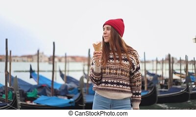 Young woman eating the icecream near the blue gondoliers - Mid shot