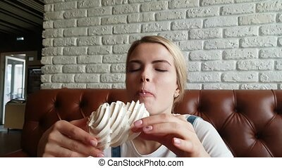 Young Woman Eating the merenge Cake - Pretty blond girl...