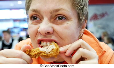 Young woman eats fast food in cafe restaurant - Young woman...