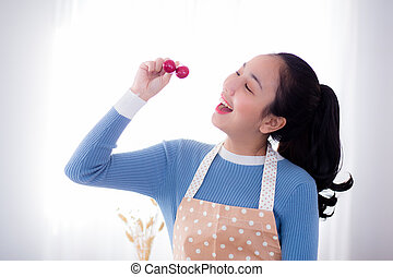 young woman eats fresh grapes in kitchen at home.