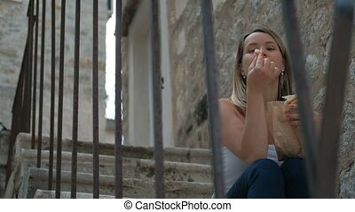 Young woman eats pastries sitting on stone staircase outdoors.