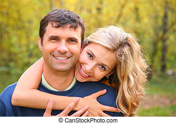 Young woman embraces man from back in autumn wood
