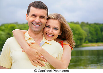 young woman embraces  man from back