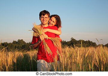 young woman embraces man from behind in wheat field