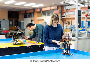 Young woman engineer working on robotics project