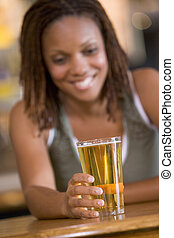 Young woman enjoying a beer at a bar