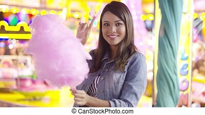 Young woman enjoying a bite of candy floss - Young woman...