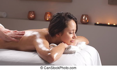 Young woman enjoying a massage in spa center.