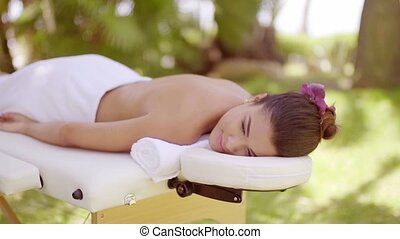 Young woman enjoying an outdoor spa treatment at a tropical...
