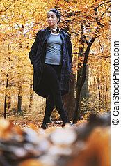 young woman enjoying autumn walk in the woods
