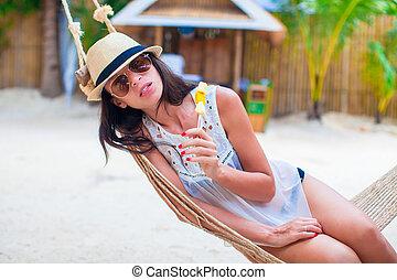 Young woman enjoying beach vacation in the hammock