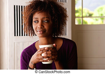 Young woman enjoying cup of coffee at home