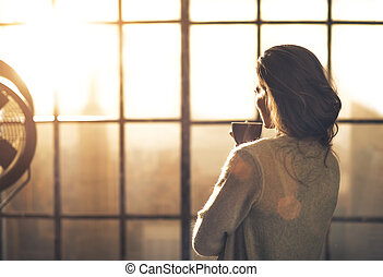 Young woman enjoying cup of coffee in loft apartment. rear ...