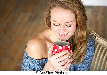 Young woman enjoying cup of tea at home