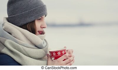 Young woman enjoying her morning coffee or tea on the background of a snowy horizon while walking